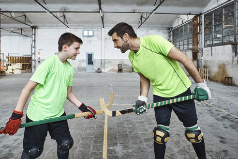 Father and son holding hockey sticks while standing face to face while playing on court - VEGF02830