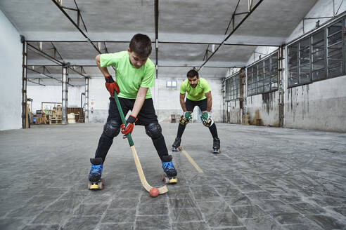 Mature man looking at son playing roller hockey on court - VEGF02842