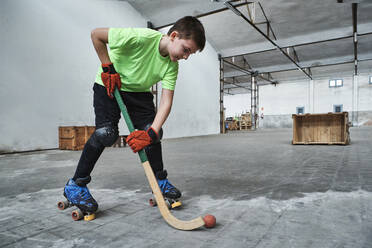 Boy practicing roller hockey during training at court - VEGF02845
