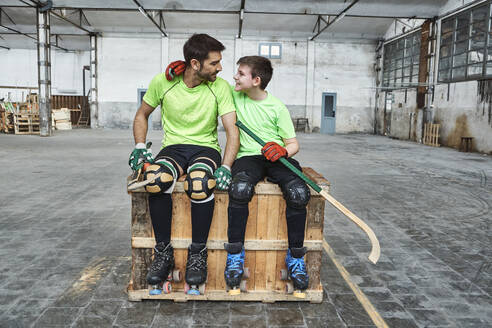 Smiling boy with arm around father while sitting with hockey sticks on wooden box at court - VEGF02848
