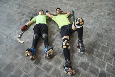 Tired father and son lying on floor after practicing roller hockey at court - VEGF02854