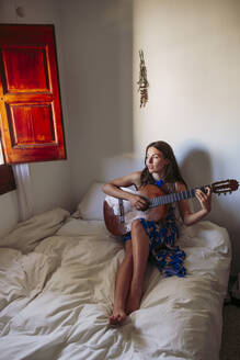 Young woman looking away while practicing guitar on bed at home - LJF01758