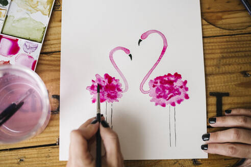 Close-up of woman hand painting flamingo animal on paper - XLGF00468