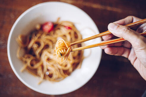 From above soft focus of crop person holding shrimp by wooden chopsticks while enjoying noodles on blurred background - ADSF12556