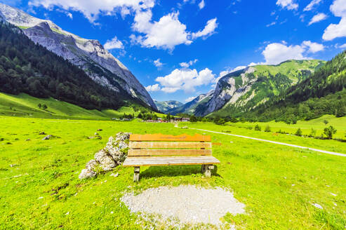 Austria, Tyrol, Vomp, Empty bench in Lower Inn Valley with village in distant background - THAF02812