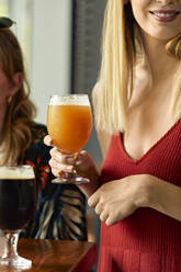 Woman holding glass of craft beer in a pub - ZEDF03631
