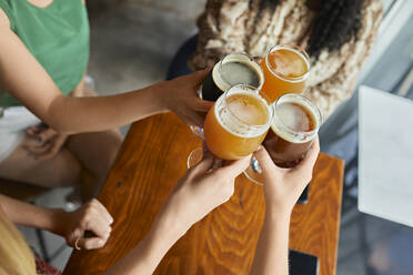 Female friends clinking craft beer glasses in a pub - ZEDF03634