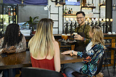 Waiter serving craft beer for female friends in a pub - ZEDF03640
