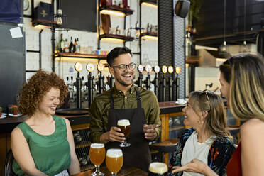 Waiter serving craft beer for female friends in a pub - ZEDF03643