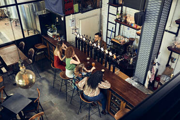 Female friends socializing at the counter in a pub - ZEDF03649