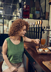 Woman having tapas at the counter in a pub - ZEDF03667