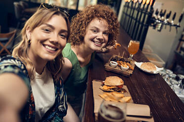 Happy female friends socializing in a pub taking a selfie - ZEDF03670