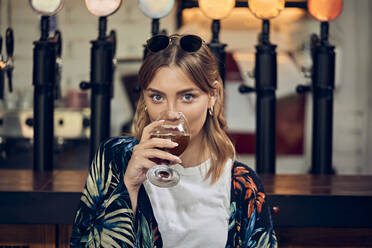 Portrait of a smiling woman in a pub having a beer - ZEDF03679