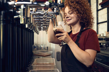 Female barkeeper tapping beer in a pub - ZEDF03691