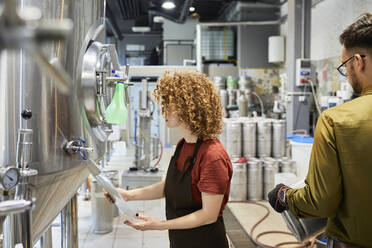 Man and woman working in craft brewery - ZEDF03694