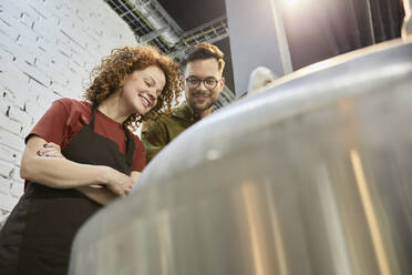 Man and woman working in craft brewery looking into tank - ZEDF03697
