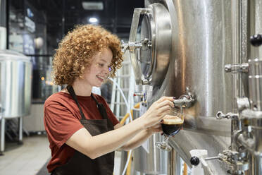 Woman working in craft brewery tapping beer from tank - ZEDF03703