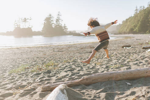 Boy with arms outstretched jumping at beach - CMSF00124