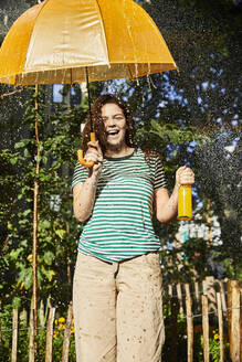Young laughing woman with umbrella and limonade in garden - FMKF06296
