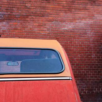 Rear windshield of red car parked in front of brick wall - NGF00602