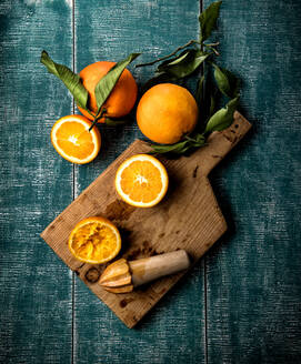 From above of ripe oranges placed on cutting board in kitchen with manual fruit squeezer - ADSF12929