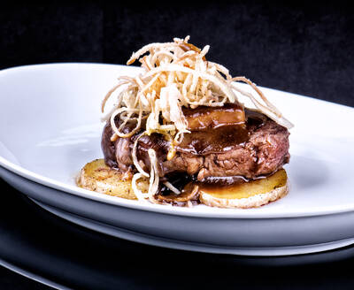 Delectable fried steak garnished with mushrooms and served with potato on dish in luxury restaurant - ADSF12959