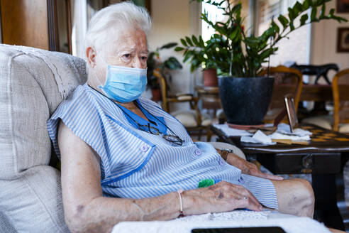Female senior with protective mask sitting in armchair at home - GEMF04094