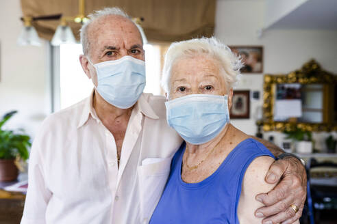 Senior couple wearing protective masks at home - GEMF04097
