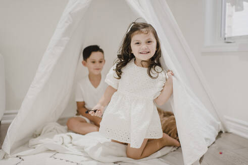 Smiling sister with brother kneeling in tent at home - SMSF00199