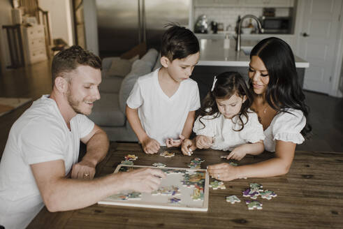 Smiling parents solving puzzle with kids over table at home - SMSF00208