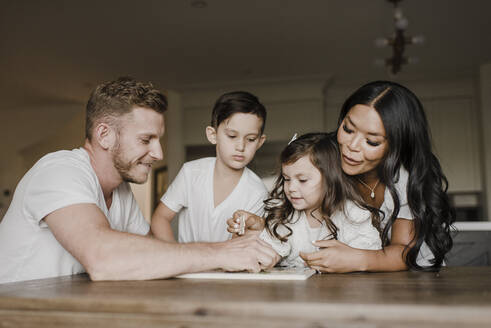 Smiling parents solving jigsaw puzzle with kids on table at home - SMSF00211
