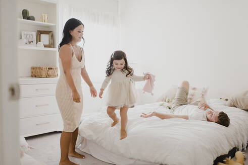 Smiling parents looking at daughter standing on bed at home - SMSF00214