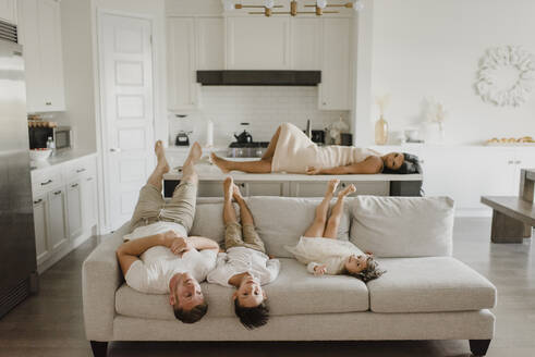 Father lying with kids on sofa while mother relaxing over kitchen island at home - SMSF00229
