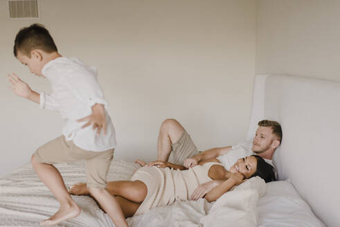 Playful son running on bed while parents lying in bedroom - SMSF00235
