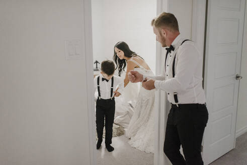 Mother dressing son for wedding while father standing in doorway at home - SMSF00244