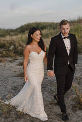 Smiling newlywed holding hands while walking in field - SMSF00247