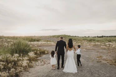 Parents and children wearing wedding dress while walking in field against sky - SMSF00253