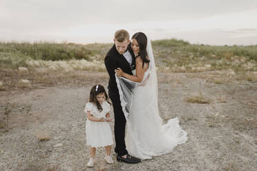 Parents with daughter in wedding dress standing against sky - SMSF00256