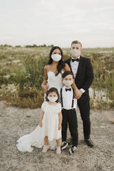 Parents and children in wedding dress wearing protective face mask while standing in field during COVID-19  - SMSF00265