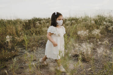 Cute girl wearing protective face mask walking in field - SMSF00271