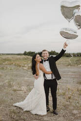Bride and groom with heart shape balloons standing against sky - SMSF00280