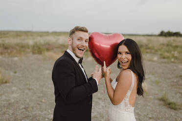 Happy bride and groom showing heart shape balloon against sky - SMSF00286