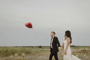 Bride and groom with heart shape balloon holding hands while walking against clear sky - SMSF00289