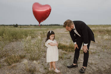 Father talking to sad daughter with heart shape balloon in field against clear sky - SMSF00292