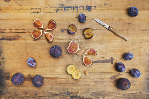 Freshly harvested figs and plums on wooden surface - GWF06741