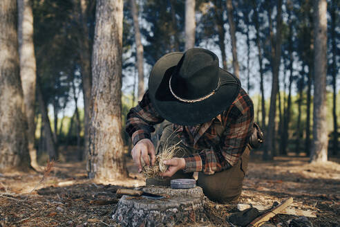 Bushcrafter preparing fire to cook food in forest - SASF00030