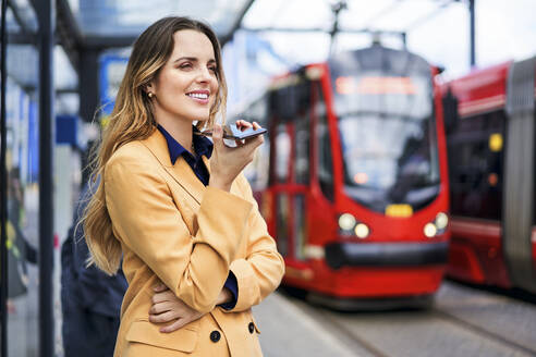 Smiling woman using speaker while talking through mobile phone at tram station - BSZF01617