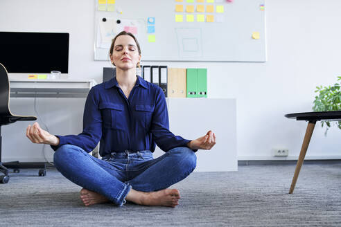 Creative businesswoman meditating in office - BSZF01650