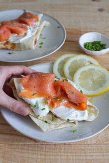 High angle of crop person having lunch and taking flatbread with sour cream and salmon slice garnished with green onion and lemon - ADSF13095