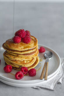 Stack of tasty pancakes with ripe raspberries placed on plate near spoons on gray background - ADSF13098